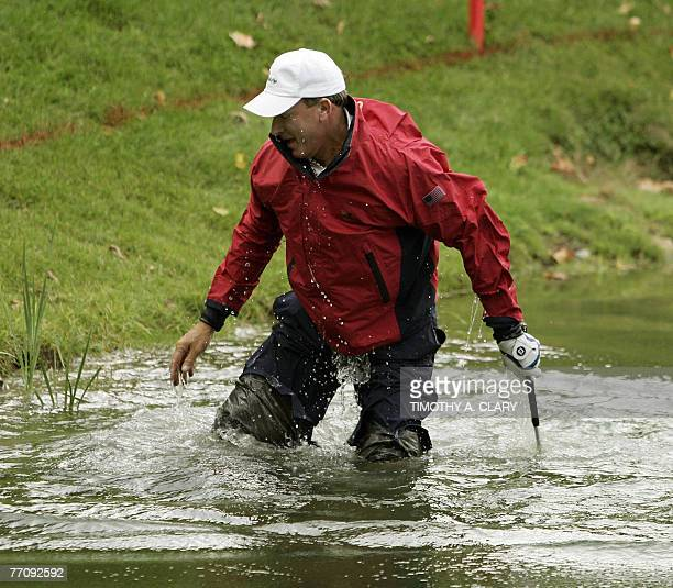 United States golfer Woody Austin gets up after hitting out of the water and falling on the 14th hole during the Four-Ball Matches of The Presidents...