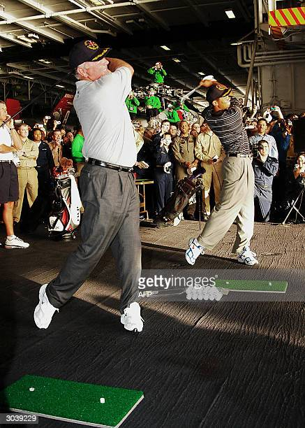 United States golfers Mark O'Meara and Tiger Woods drive golf balls through a door off the hangar bay deck aboard the USS George Washington Tiger...