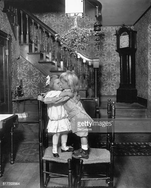 United States Holidays and how children celebrated them Christmas Children standing on chairs kiss under the mistletoe in a New England home Undated...