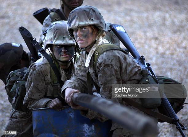 United States Marine Corps female recruits try to extend a steel pole to a cross bar January 15 2003 during the Leadership Reaction Course which is...