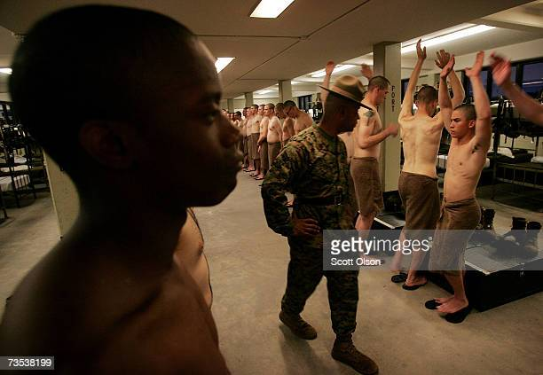 United States Marine Corps recruit senior drill instructor Staff Sergeant Hugo Cherena of Waterbury Connecticut inspects his recruits for injuries...