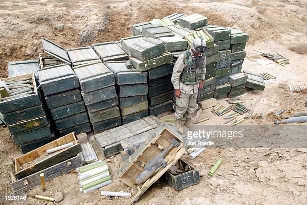 United States Marine from Task Force Tarawa looks at a cache of weapons found near an Iraqi military facility April 12 2003 near Al Kut Iraq The...