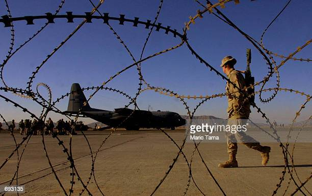United States Marine is seen through barbed wire walking past an Air Force C130 Hercules transport/cargo plane on the American military compound at...