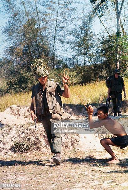 United States Marine of the 1st Battalion, 1st Marine Regiment, 1st Marine Division, leads a Vietcong suspect awaiting transport for questioning...