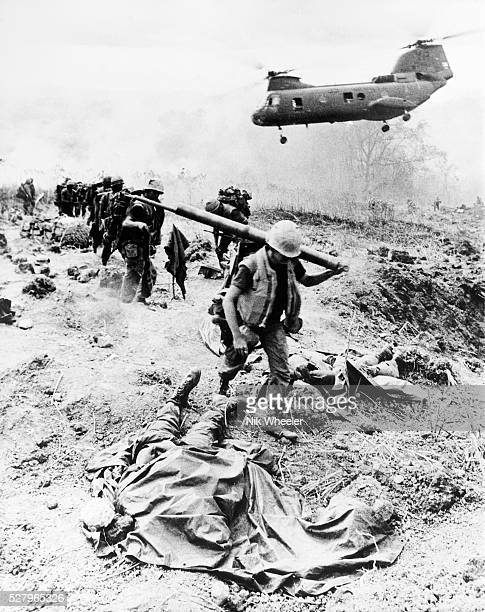 United States Marine troops on operation near the Demilitarized Zone in I Corps near the border with North Vietnam walk past covered body of dead...