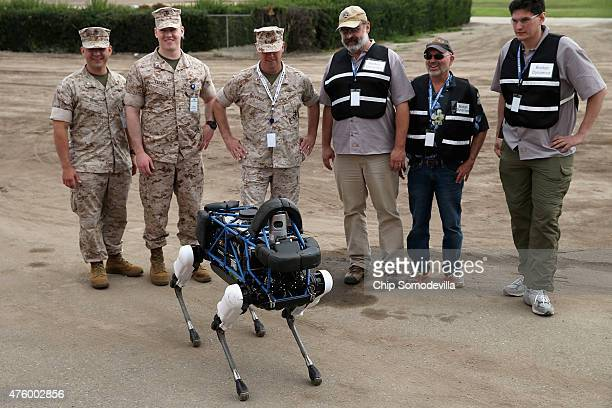 United States Marines and representatives from Boston Dynamics look at Spot a fourlegged robot designed for indoor and outdoor operation during the...