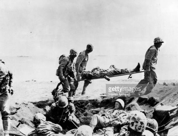 United States Marines carry a wounded soldier on a stretcher along a beach during the Battle of Iwo Jima, Iwo Jima, Japan, 1945.