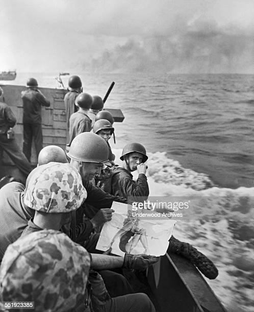 United States Marines on a landing barge share viewing a pinup girl as they approach the Japanese held island of Tarawa Gilbert Islands 1943