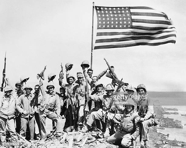 United States Marines pose on top of Mount Suribachi on the island of Iwo Jima with the American flag