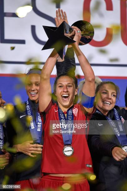 United States midfielder Carli Lloyd celebrates with teammates by raising the SheBelieves Cup trophy after the SheBelieves Cup match between USA and...