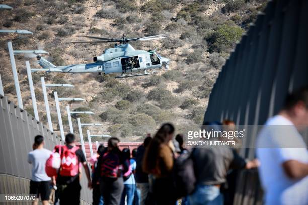 A United States Military helicopter flies past a pedestrian bridge after the closing of the United StatesMexico border was ordered on November 25...