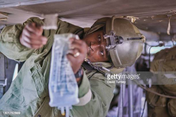 United States military personnel unclipping an IV bag from its ceiling clip in a Sikorsky UH-60 Black Hawk helicopter on their arrival at the 5th...