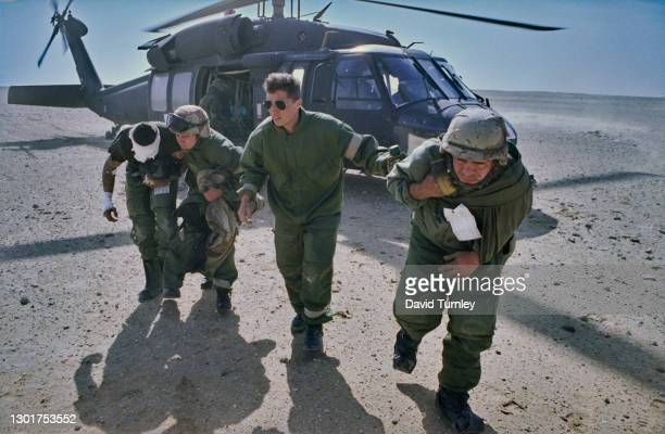 United States military personnel with an injured colleague, their arm and head in bandages, with a Sikorsky UH-60 Black Hawk helicopter in the...