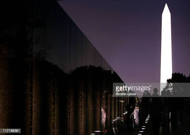 United States National Monuments Veterans Day A visitor to the Vietnam War Memorial places a hand on the wall engraved with the names of the...