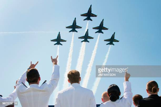 United States Naval Academy midshipmen cheer as the US Navy's Blue Angels fly over the graduation ceremony in Annapolis Maryland on May 25 2018