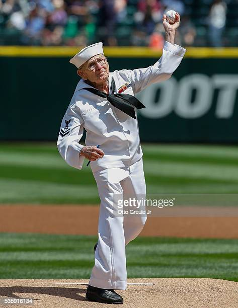 United States Navy 2nd Class Petty Officer Mr Burke Waldron throws out the ceremonial first pitch prior to the game between the Seattle Mariners and...