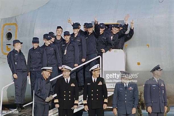 United States Navy captain Lloyd M Bucher pictured bottom left with members of the crew of USS Pueblo on their arrival at Kimpo International Airport...