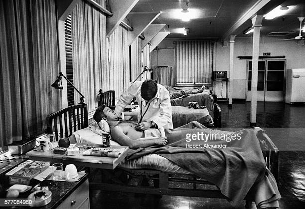 United States Navy medical doctor tends to a bedridden patient an enlisted Navy petty officer at an infirmary at the Atsugi Naval Air Station near...