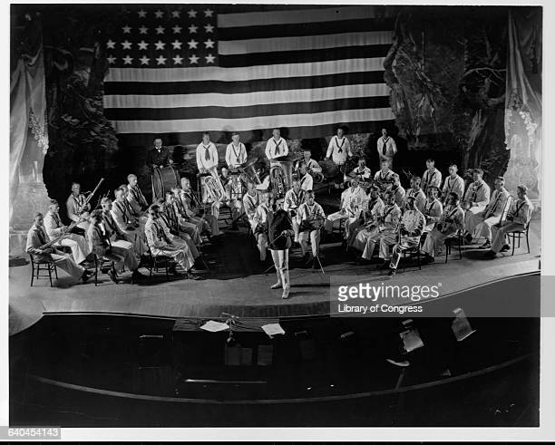 A United States Navy recruiting band sits onstage under an American flag at Potter Theater