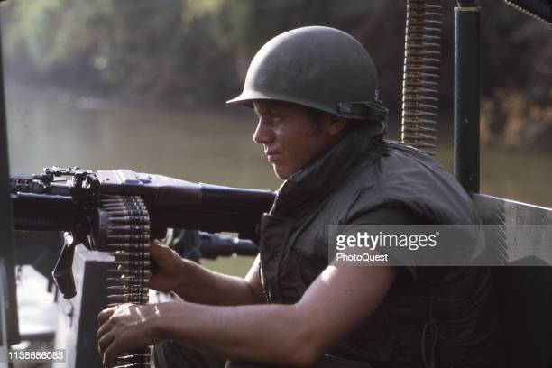 A United States Navy River Patrol Boat crewman mans an M60 machine gun aboard the boat during Operation Big Muddy on the Saigon River Dau Tieng...