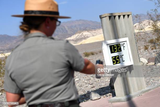 United States Park Ranger Jeannette Jurado takes a surface temperature reading from an unofficial thermometer reading 132 degrees Fahrenheit/55...