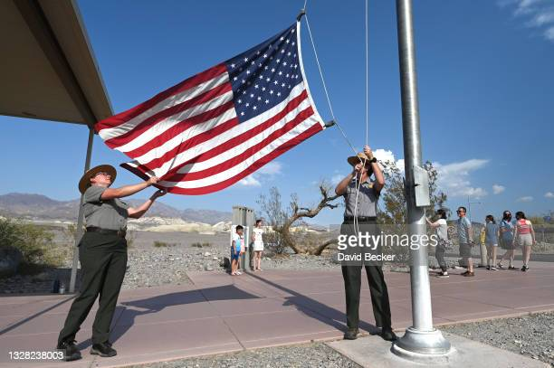 United States Park Rangers Jeannette Jurado and Maureen Lavelle lower the American flag as people line up to photograph an unofficial thermometer at...