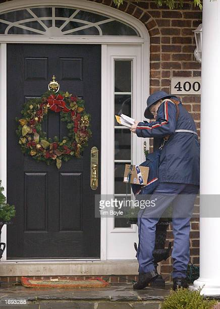United States Post Office letter carrier John Miller delivers mail December 18, 2002 to a holiday-decorated home along his route in Park Ridge,...