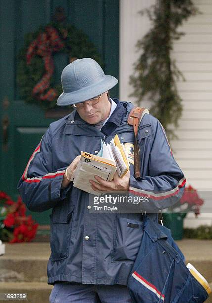 United States Post Office letter carrier John Miller departs a holiday-decorated home after delivering mail December 18, 2002 along his route in Park...