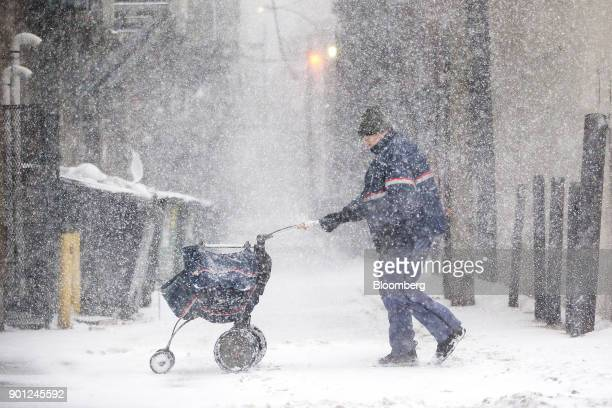 A United States Postal Service letter carrier delivers mail during a snow storm in Boston Massachusetts US on Thursday Jan 4 2018 A fastmoving winter...