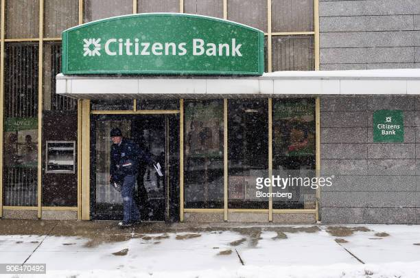 A United States Postal Service letter carrier exits from a Citizens Financial Group Inc bank branch as snow falls in downtown Portsmouth Ohio US on...