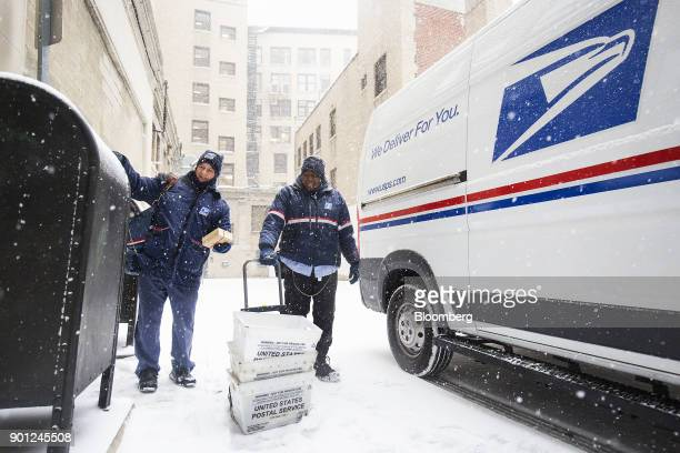United States Postal Service letter carriers deliver mail during a snow storm in Boston Massachusetts US on Thursday Jan 4 2018 A fastmoving winter...
