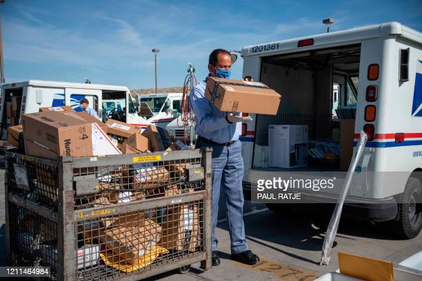 United States Postal Service mail carrier Frank Colon loads his truck and organizes packages for his route amid the coronavirus pandemic on April 30,...