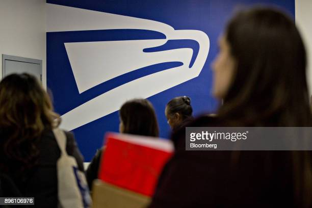 United States Postal Service signage stands past customers at the USPS Suburban post office station in Gaithersburg Maryland US on Tuesday Dec 19...