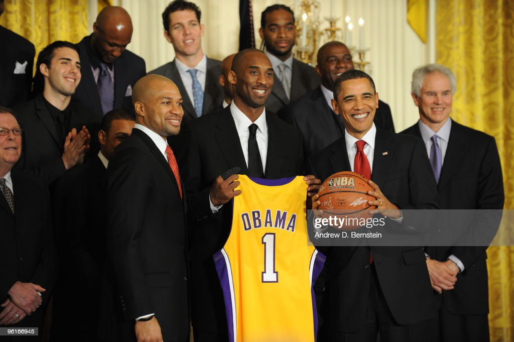 United States President Barack Obama accepts a jersey and basketball from Lakers captains Derek Fisher (left) and Kobe Bryant (center) during a ceremony to honor the 2008-9 NBA Champions in the East Room of the White House on January 25, 2010 in Washington, DC.