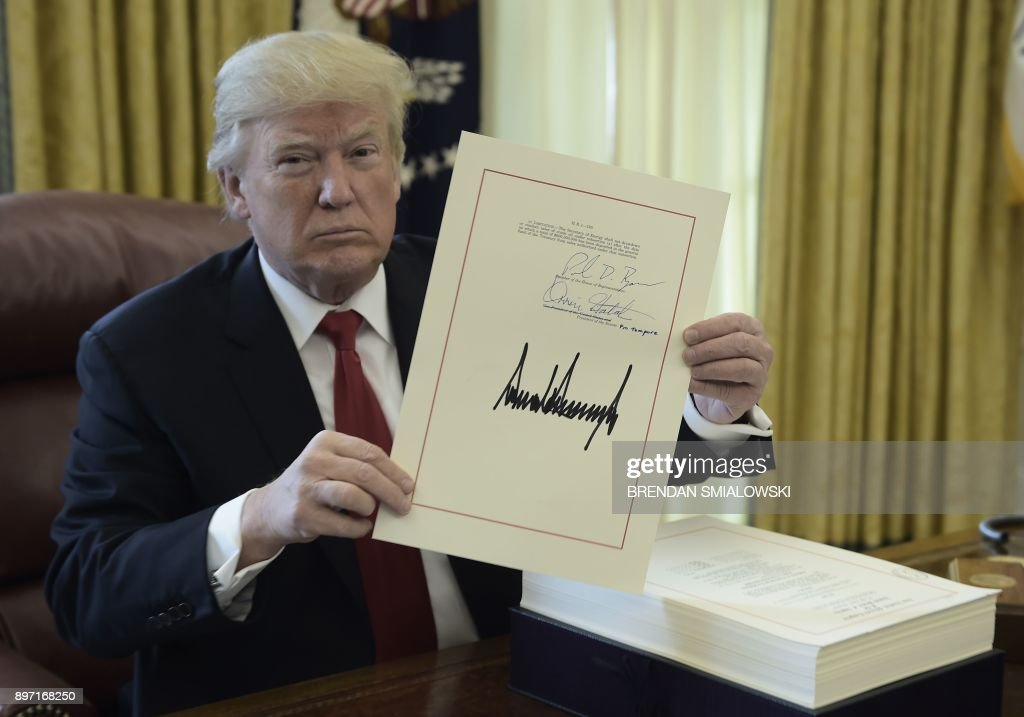 TOPSHOT - United States President Donald J. Trump holds up a document during an event to sign the Tax Cut and Reform Bill in the Oval Office at The White House in Washington, DC on December 22, 2017. / AFP PHOTO / Brendan SMIALOWSKI