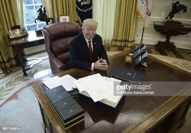 United States President Donald J Trump prepares to sign the Tax Cut and Reform Bill in the Oval Office at The White House in Washington DC on...