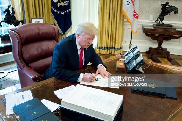 United States President Donald J Trump signs the Tax Cut and Reform Bill in the Oval Office at The White House in Washington DC on December 22 2017 /...