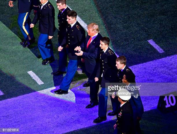 United States President Donald Trump is escorted onto the field for the national anthem before CFP the National Championship presented by ATT between...
