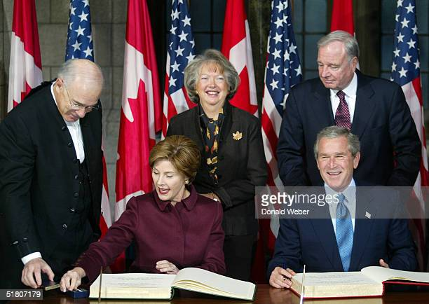 United States President George W Bush and First Lady Laura Bush sign the Distinguished Visitors Book while Canadian Prime Minister Paul Martin and...