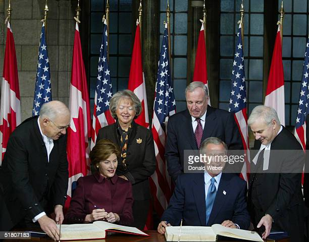 United States President George W Bush and First Lady Laura Bush sign the Distinguished Visitors Book while Canadian Prime Minister Paul Martin his...
