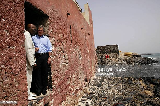 """United States President George W. Bush and Senegal President Abdoulaye Wade look out the """"door of no return"""" at the slave house on Goree Island off..."""