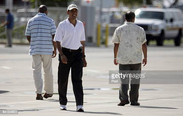 United States Presidentelect Barack Obama smiles as he gets ready to board his chartered flight for Chicago January 1 2009 at Honolulu International...