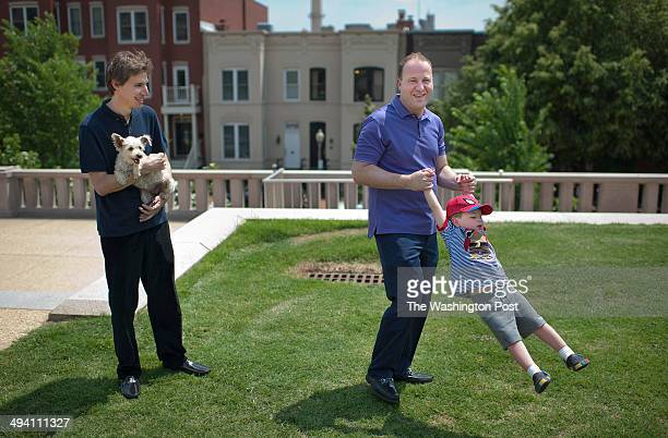 United States Representative Jared Polis right center spins his son Caspian as they pose for a portrait along with Polis' partner Marlon Reis left...