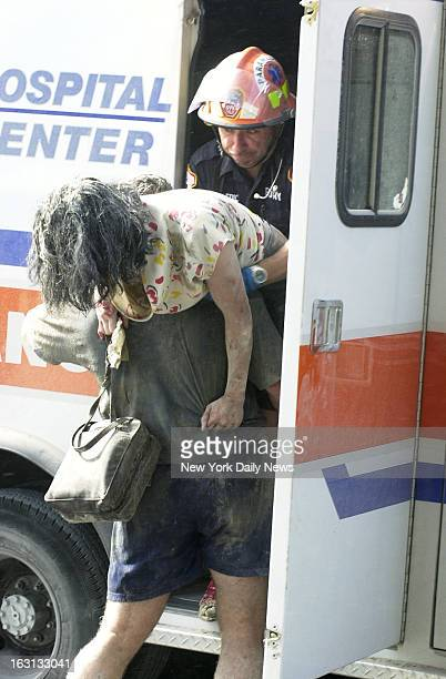 United States Secret Service Agent Thomas Armas, carries an injured woman to an ambulance after Tower One of World Trade center collapsed.