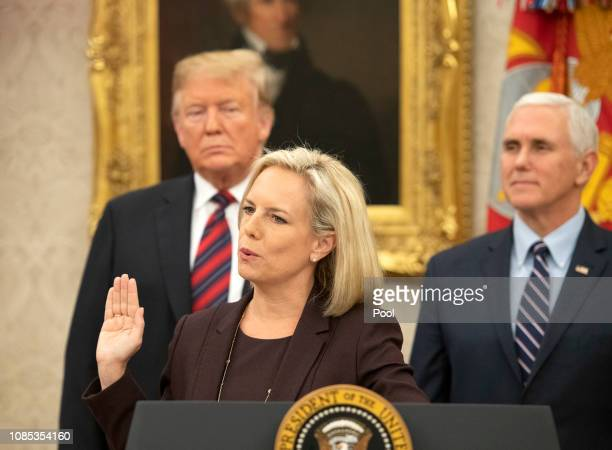 United States Secretary of Homeland Security Kirstjen Nielsen center administers the oath of citizenship to five people as US President Donald Trump...