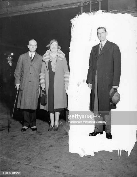 United States Secretary of the Interior Ray Lyman Wilbur and his wife at the Northwest railroad station with an unidentified man isolated by a masked...