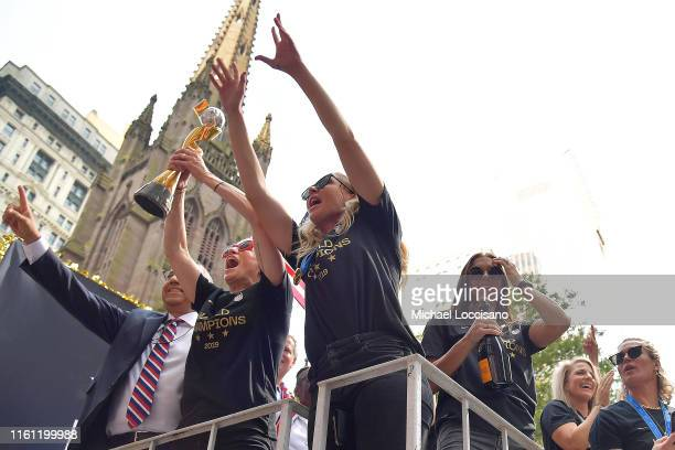 United States Soccer Federation president Carlos Cordeiro Megan Rapinoe Allie Long and Alex Morgan celebrate and hold up the trophy while riding on a...
