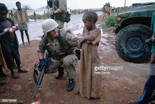 A United States soldier attempts to talk with a shy Somali boy during 'Operation Restore Hope' In the 1980s a civil war in Somalia began when warlord...