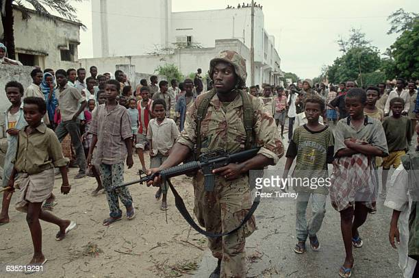 United States soldier is followed by a group of curious Somali chilidren while he patrols along the Green Line which is a heavily contested area...