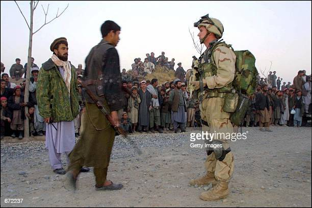 United States Special Operations soldier stands guard as civilians look on and Northern Alliance fighters help to coordinate a visit by a US official...